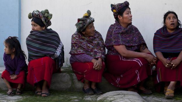 Vier Frauen und ein Mädchen des indigenen Volkes der Ixil sitzen auf einem Gehsteig in der guatemaltekischen Stadt Nebaj.