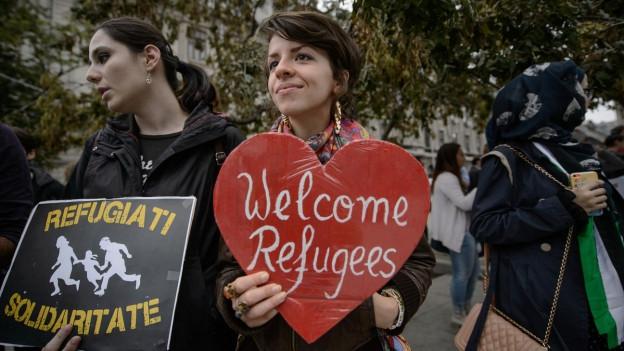 Eine junge Frau hält bei einer Kundgebung in der rumänischen Hauptstadt Bukarest ein herzförmiges Schild hoch mit der Aufschrift «Flüchtlinge willkommen».