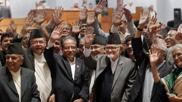 Aufnahme von Abgeordneten im nepalesischen Parlament winken in die Kamera.