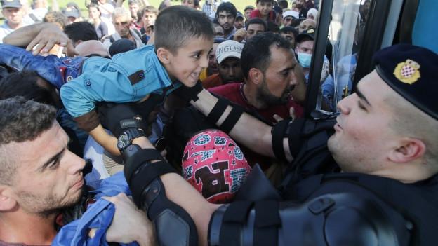 Zu sehen ist ein kroatischer Polizist im Grenzort Tovarnik, der Flüchtlingen hilft, einen Bus zu besteigen. Bild vom Donnerstag, dem 17. September.