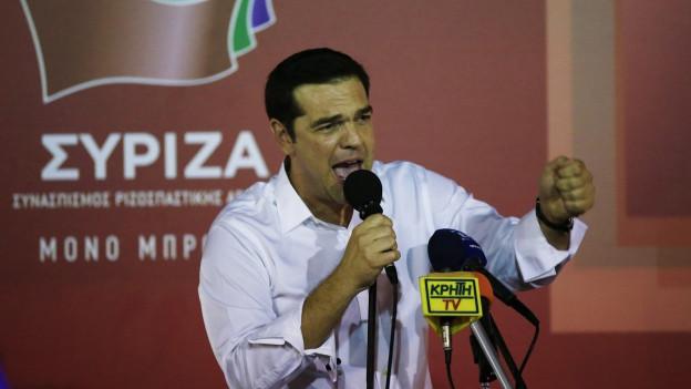 Alexis Tsipras hält eine Rede an einem Pult, in der einen Hand hält er ein Mikrofon, die andere Hand hat er zu einer Faust geballt.