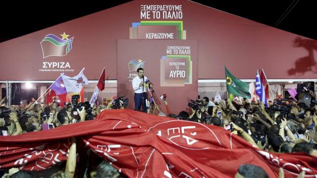 Alexis Tsipras auf einer Bühne mit Syriza Logos, im Vordergrund sind fiele Menschen, die den Wahlsieg von Syriza feiern.