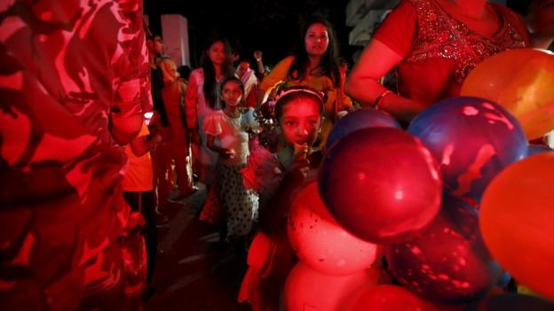 Ein von Scheinwerfern rötlich eingefärbtest Bild, auf dem Menschen mit Ballons vorbeiziehen.