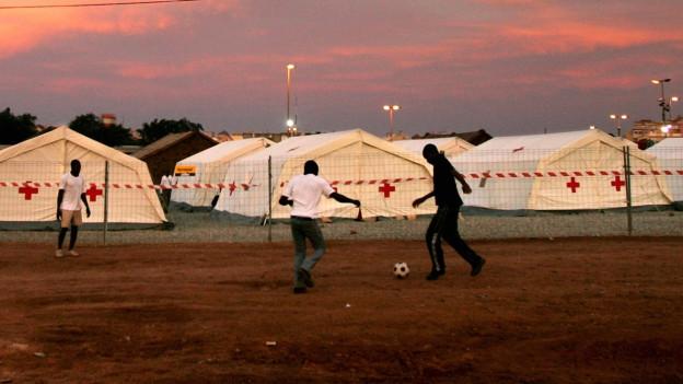 Afrikaner spielen Fussball vor Zelten.