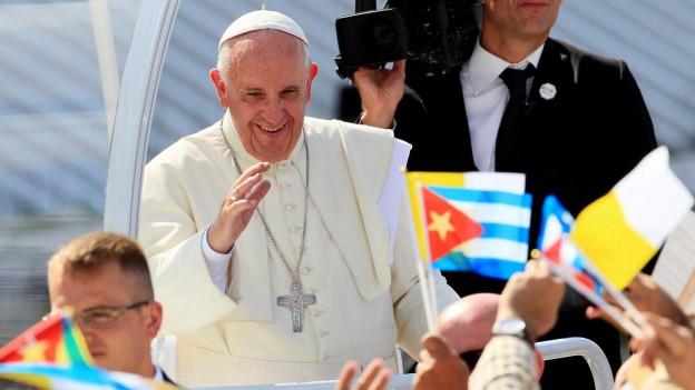 Der Papst steht auf dem Papamobil und wird umringt von Menschen, die kubanische Fähnchen schwenken.