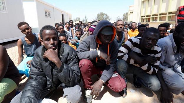 Junge Afrikaner sitzen auf einem Platz (im Hintergrund Baracken).