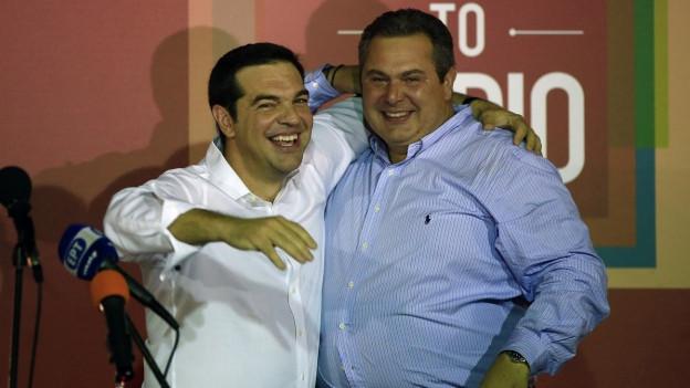 Zwei Männer umarmen sich und lachen in die Kamera.