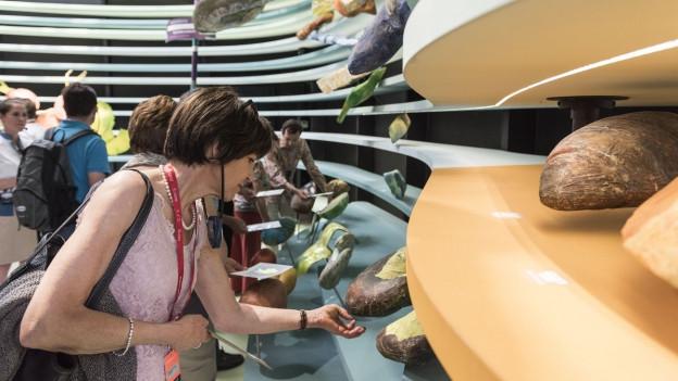 Aufname einer Besucherin im deutschen Expo-Pavillon, die die Ausstellung gegutachtet.