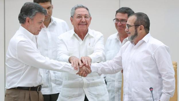 Der kubanische Präsident Raul Castro (in der Mitte) steht zwischen dem kolumbianischen Präsidenten Juan Manuel Santos und Farc-Chef Rodrigo Londono, besser bekannt unter seinem Übernamen Timoschenko. Santos und Timoschenko geben sich vor den Medien die Hand.