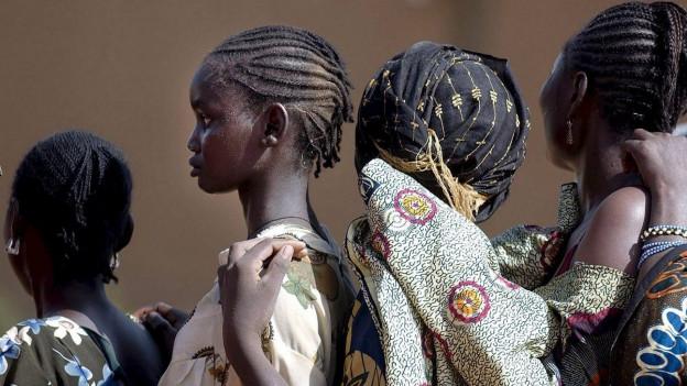 Aufnahme von Frauen aus Niger in traditioneller Kleidung, die in einer Schlange anstehen.