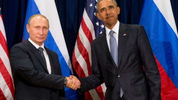 Zwei Männer geben einander die Hand (im Hintergrund Flaggen der USA und Russlands).