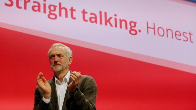 Mann steht vor einer Wand und applaudiert.