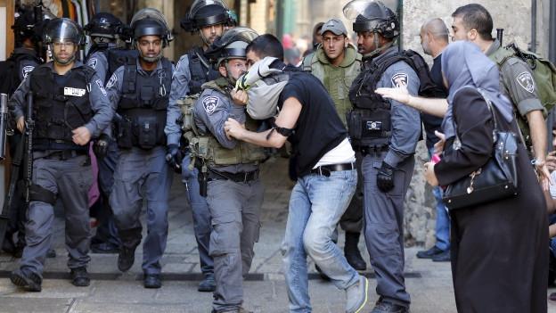 Polizisten in Kampfmontur ringen mit einem jungen Mann.