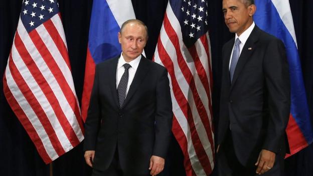 Zwei Männer vor amerikanischer und russischer Flagge.