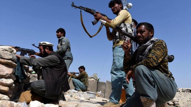 Bewaffnete Männer kauern auf einem Hügel