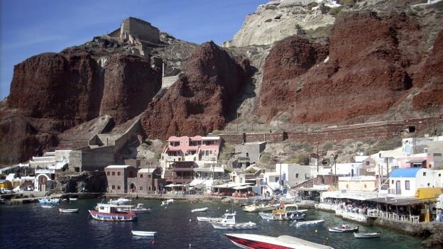 Häuser in karger Insellandschaft vor Meer.