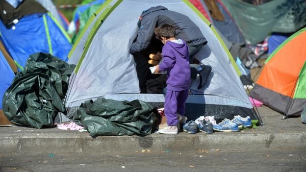 Kind vor einem Zelt.