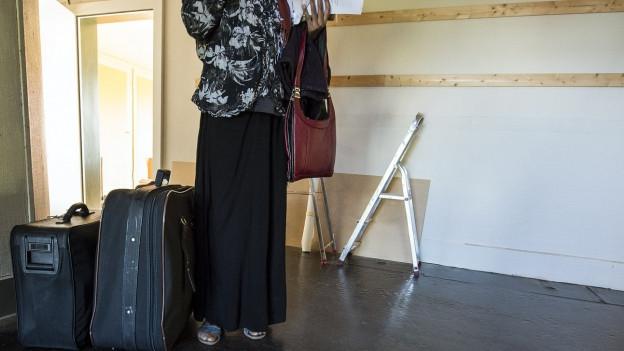 Eine Asylbewerberin tritt in ein Asylzentrum in der Schweiz ein