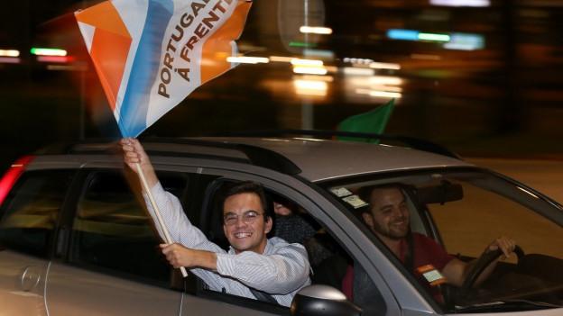 Ein Anhänger der Konservativen schwingt die Fahne der Partei aus einem fahrenden Auto heraus.
