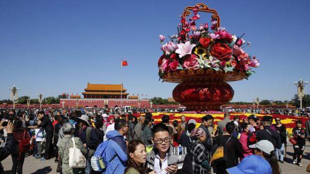 Aufnahme von chinesischen Touristen, die in Peking den Tiananmen-Platz besuchen.