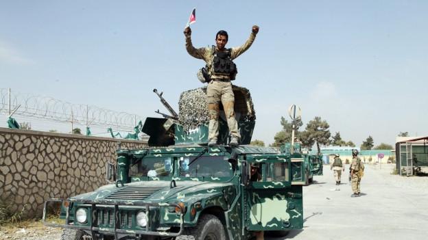 Aufnahme eines afghanischen Soldaten, der auf einem Auto steht und ein Fähnchen schwingt.