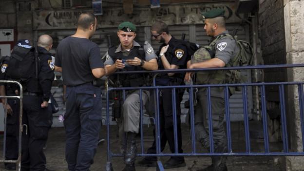 Aufnahme eines israelischen Soldaten, der bei einer Absperrung die Papiere eines Passanten überprüft.