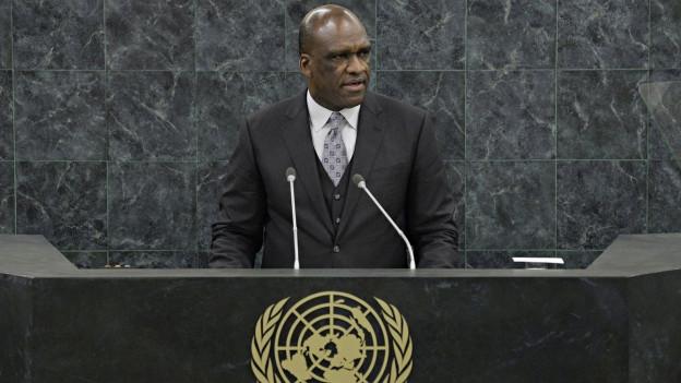 John Ashe hält eine Rede auf dem Podium im Plenarsaal der UNO in New York.