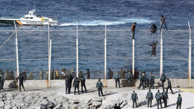 Flüchtlinge sitzen auf einem mit Stacheldraht gesicherten Zaun.