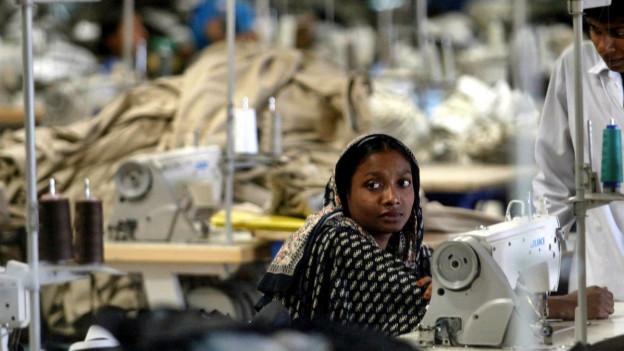 Eine junge Frau sitzt in einer Textilfabrik in der Nähe von Dhaka, Bangladesch, an ihrem Arbeitsplatz vor einer Nähmaschine.