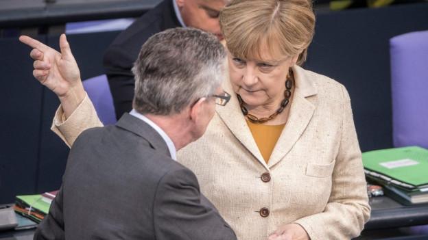 Kanzlerin Merkel spricht mit Innenminister de Maizière im deutschen Bundestag, er ist von hinten zu sehen, steht ihr gegenüber (1. Oktober 2015).