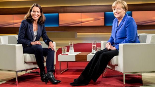 Kanzlerin Merkel und Moderatorin Anne Will vor der Sendung, sie sitzen sich im Studio gegenüber (7. Oktober 2015).