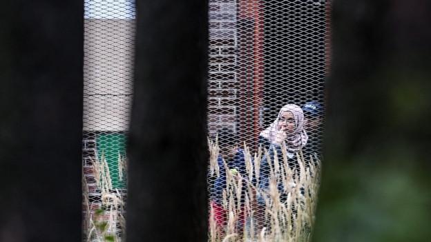 Flüchtlinge vor einem Haftzentrum im tschechischen Bela-pod-Bezdezem, man sieht eine Frau mit Kopftuch und ein Kind hinter einem engmaschigen Zaun (6. September 2015).