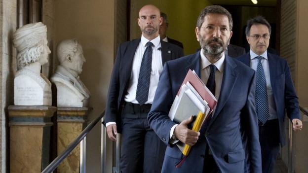 Ignazio Marino schreitet mit Akten unter dem Arm durch die Hallen des Campidogli.
