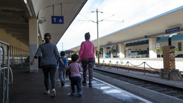 Zwei Frauen laufen mit Kindern dem Perron entlang.