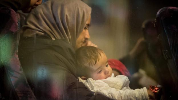 Eine Frau mit Kopftuch hält ihr Kleinkind in den Armen