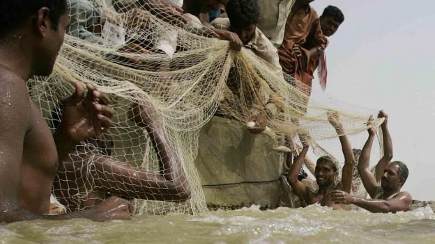 Zu sehen ist eine Gruppe von pakistanischen Männern, die während einer Hochwasserkatastrophe mit einem Boot ihr Hab und Gut zu retten versuchen.