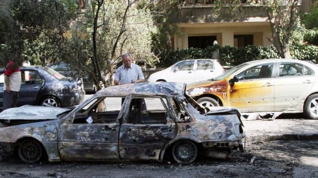 Aufnahme eines Mannes, der hinter einem ausgebrannten Auto steht.