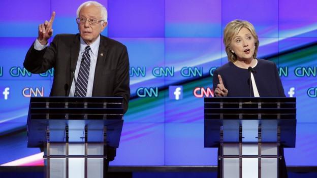 Hillary Clinton und ihr interner Herausforderer stehen hinter Rednerpulten auf einem Podest, beide mit erhobenem Zeigfinger