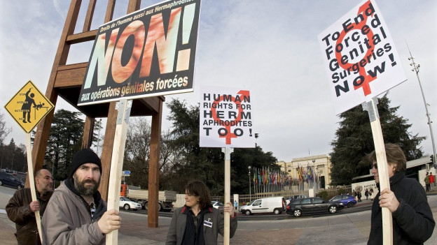 Menschen mit Protest-Plakaten (im Hintergrund Gebäude).