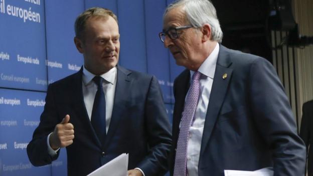 Donald Tusk und Jean Claude Juncker sprechen miteinander vor einer blauen Wand. Beide haben einen Stapel Papiere in der Hand bzw. unter dem Arm.