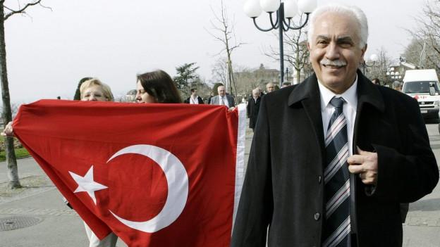 Der türkische Politiker Perincek, hinter ihm tragen zwei Frauen eine türkische Flagge.