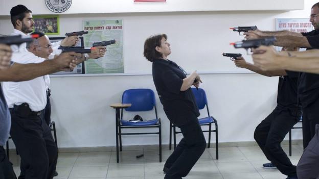Israelis halten Pistolen in der Hand und zielen aufeinander.
