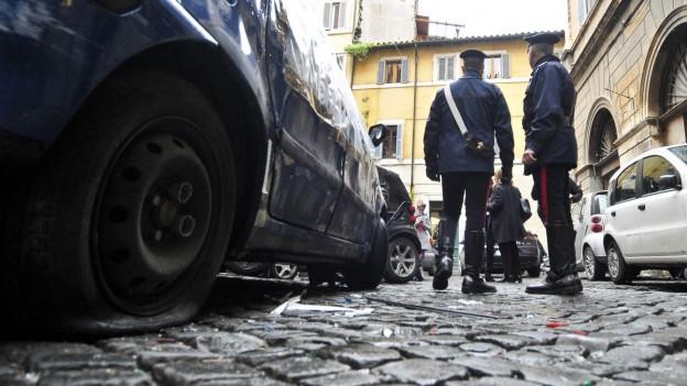Zwei italienische Polizisten stehen links neben einem Polizeiauto in einer Gasse in einem italienischen Städtchen.