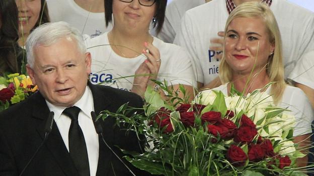 ^Jaroslaw Kaczynski, steht am Rednerpult und wird umringt von applaudierenden Frauen. Im Vordergrund steht ein Blumenstrauss mit Rosen.