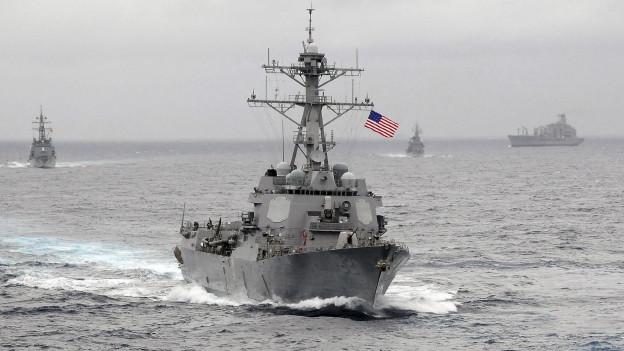Archivaufnahme eines amerikanischen Kriegsschiffes. Es ist auf dem offenen Meer, der Himmel ist bewölkt, im Hintergrund sind weitere Schiffe.