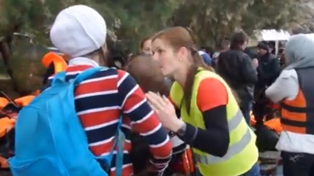 Eine Frau hält ein Kind auf dem Arm und spricht mit einer Helferin.