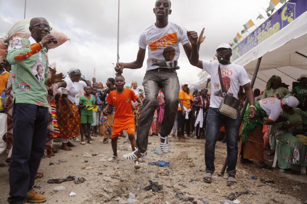 Anhänger von Präsident Ouattara feiern den Wahlsieg in Abidjan, ein Mann mit einem Ouattara-T-Shirt springt in die Luft, ein anderer steht mit einem Mikrofon daneben (28. Oktober 2015).