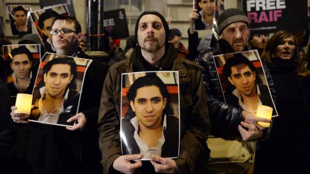 Eine Gruppe von Aktivisten steht im Januar 2015 vor der saudi-arabischen Botschaft in London und hält Plakate mit dem Porträt von Raif Badawi.