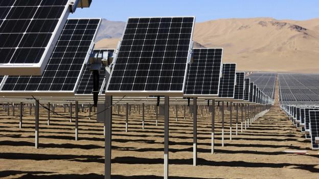 Das Bild zeigt ein Feld von Solaranlagen in einer Wüste.