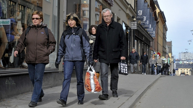 Drei Menschen mit Einkaufstaschen laufen durch eine Strasse.